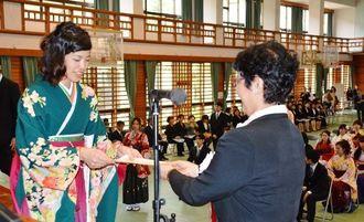 前田和子学長から証書を受け取る卒業生=15日、那覇市与儀の県立看護大学体育館