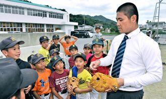母校の学童野球チームの子どもたちを激励する内間拓馬投手(右)=24日、本部町東・本部小学校(金城健太撮影)