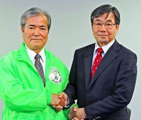 名護市長選を前に、健闘を誓い握手を交わす稲嶺進氏(右)と末松文信氏=7日午前、名護市・産業支援センター