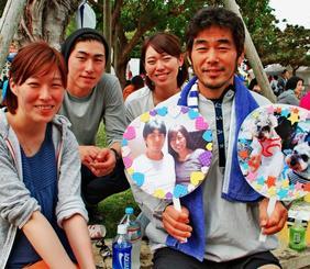 亡き妻西尾道子さんとの2ショット写真を手に「来年は完走」と誓う(右から)康司さんと、あずささん、泉樹さん、桑川かえでさん=4日、奥武山公園