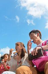 照り付ける日差しの下でソフトクリームを頬張る観光客=26日午後、那覇市久茂地・国際通り