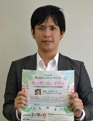 シンポジウムへの参加を呼び掛ける渡久地準事務局長=1月31日、沖縄タイムス社