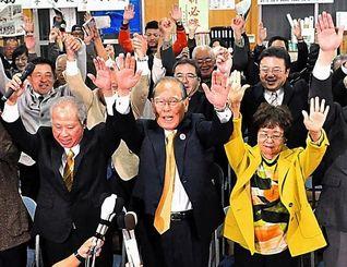 当確の報道を受け、万歳する照屋寛徳氏(中央)=14日午後8時2分、宜野湾市長田の選挙事務所