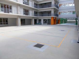 子どもたちが運動する際に使う中庭。後方にある床にはクッションゴムが敷かれている=8日、那覇市立上間小学校(那覇市教育委員会提供)
