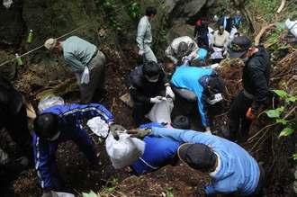 国立沖縄戦没者墓苑近くに不法投棄されたごみを回収するボランティアら=28日、糸満市摩文仁