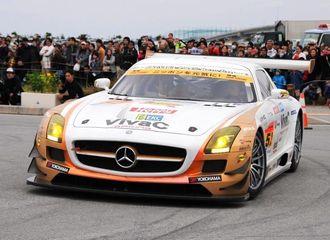 エンジンの重低音を響かせ、県内で初めて公道を走る沖縄IMPのレーシングカー。大勢のモーターファンがその迫力を堪能した=豊見城市豊崎
