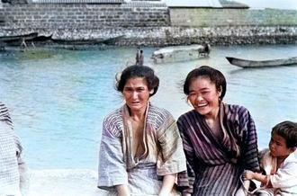 夫を待つ/糸満の港で、漁から帰る夫を待つ女性たち。右側の女性の口元から白い歯並びがのぞいている