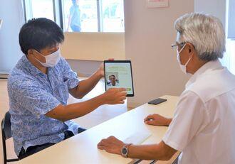 専用ウェブサイトで顔情報を登録する座喜味一幸市長(右)=9日、宮古島市役所