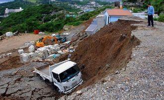 豪雨の影響で土砂崩れが起き、2トントラックが滑り落ちた現場=10日午後、西原町池田(伊禮由紀子撮影)