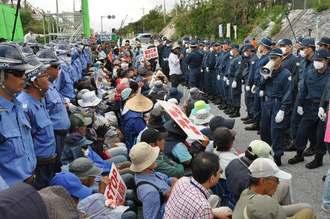 民間警備員(左)と機動隊(右)の間に座りこんで抗議する市民ら=21日正午ごろ、名護市辺野古