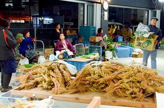 野菜や正月のしめ縄などを並べ、相対売りする関係者たち=27日午前4時半ごろ、那覇市樋川・のうれんプラザ
