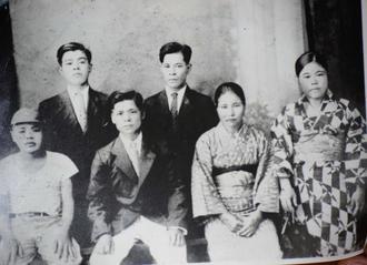 金城盛徳さん(前列左端)が17歳だったころ、テニアンで撮影された家族写真。後列左から2人目が父珍明さん