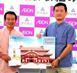 照屋堅二教育長(左)にWAONカードを贈る佐方圭二社長=4日、豊見城市役所