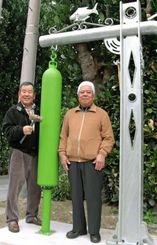 大嶺正年さん(右)が作った架台に釣り下げた鐘をたたく島袋榮一区長=12月31日、国頭村浜区