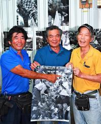 1963年に撮影された写真に父親の姿を見つけ、その写真を手に記念撮影に収まる前原盛男さん(左)と市場関係者=9日、那覇市樋川の農連市場