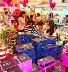 バレンタインデーを前にお気に入りのチョコレートを選ぶ女性客ら=13日午後、サンエー那覇メインプレイス