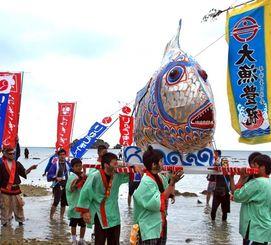 豊漁や繁栄を祈るナンザモーイで魚みこしをかつぐ住民ら=3日、うるま市