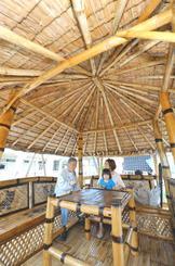 竹製の東屋の感触を確かめる来場者。リゾート施設への導入を目指している=18日、宜野湾市の沖縄コンベンションセンター展示棟