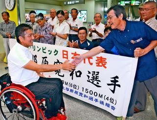 那覇空港に到着し、後援会のメンバーと握手を交わす上与那原寛和選手(左)=那覇空港