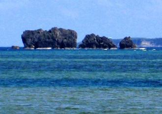 沖合いに浮かぶエーグ岩=金武町並里