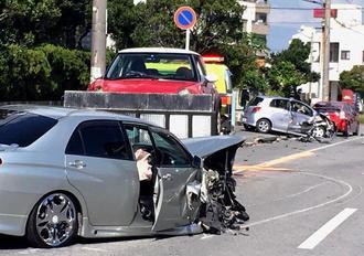 対向車線にはみ出し、正面衝突した後、スピンして停車した容疑者の乗用車(手前)=11日午後1時10分ごろ、宜野湾市野嵩