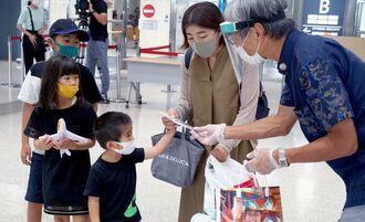 県外から到着した家族連れの観光客に感染防止対策を呼び掛けるチラシ入りマスクを手渡す、JTB沖縄の杉本健次社長(右)=18日、那覇空港