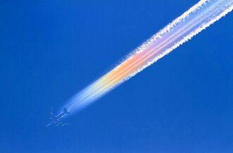 太陽光に反射して、色とりどりに輝く民間機の飛行機雲=4月29日午前9時半ごろ、北谷町・宮城海岸近くから撮影(安里駿佑さん提供)