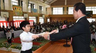山田義紀校長から卒業証書を受け取る卒業生(左)=23日午前、浦添市立仲西小学校