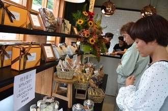 開店日に棚に並ぶ商品を品定めする客=15日、沖縄市松本の「プーゾチーズケーキセラー沖縄知花店」