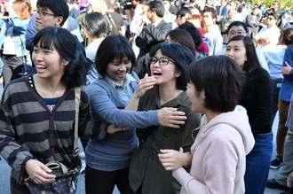 掲示板に張り出された受験番号を確認し喜ぶ受験生=7日午後、西原町・琉球大学(下地広也撮影)
