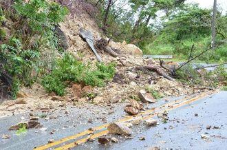 約10メートルにわたって擁壁が崩壊し、国道331号の1車線をふさいだ=24日午後3時半すぎ、名護市二見