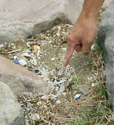 岩陰に集まったプラスチックの粒子。紫外線吸収剤が検出されることが少なくない=2018年5月、千葉市