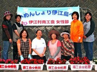 ベゴニアのプランターを設置し、「いめんしょり(ようこそ)伊江島へ」と声をそろえる村商工会女性部のメンバー=伊江港
