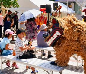 「Ship of the Ryukyu」の周知イベントで、踊る獅子舞と子どもたち=2日、那覇市文化てんぶす館前