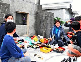 墓前で供え物を分け合う家族=7日午後、那覇市・識名霊園(落合綾子撮影)