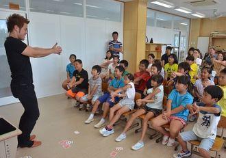 「子どももできるマジックを教えて」と頼まれ、手ほどきするMASAさん(左)=10日、渡嘉敷村・阿波連小学校