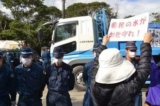資材を積んだトラックがゲート内に入っていく中、声をあげる市民ら=8日午前、東村高江