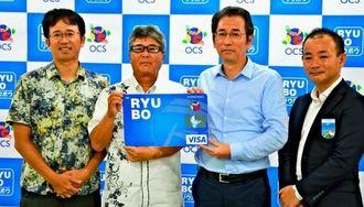リウボウOCSカード発行を発表するOCSの渡慶次道俊社長(左から2人目)とリウボウインダストリーの糸数剛一社長(同3人目)ら=11日、デパートリウボウ