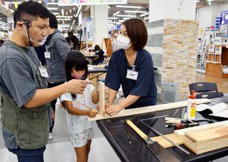 講師の島袋清成さん(左)からアドバイスをもらいブックシェルフ作りに取り組む参加者=17日、浦添市のメイクマン浦添本店