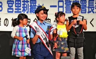 来店した子どもたちにワイヤロックを手渡したAKB48の宮里莉羅さん=20日、那覇市のイオン那覇店