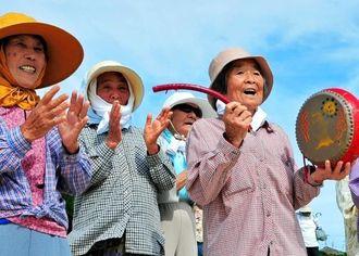 太鼓をたたき、ハーリー舟を迎える名城の女性たち=北名城ビーチ