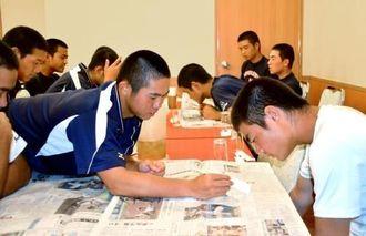 初戦突破を報じる新聞に目を通す沖縄尚学ナイン=18日、大阪市内の宿舎