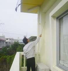 道具を使い、劣化の有無を確認する建築士(NPO沖縄県建築設計サポートセンター提供)