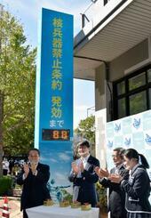 核兵器禁止条約発効までの日数が点灯したカウントダウンボードと長崎市の田上富久市長(左から2人目)ら=26日午後、長崎市役所