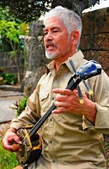 神谷門中に約250年伝わるという三線を弾く神谷清一さん。がんから回復し、芸の道を歩める感謝を豊年祭に込める=21日、八重瀬町志多伯
