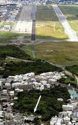 米軍普天間飛行場(上)と落下物が見つかった沖縄県宜野湾市の緑ケ丘保育園(矢印)=7月24日撮影