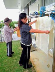 一緒に洗濯物を干すマサコさん(奥)とサポーターの我喜屋さん=那覇市内