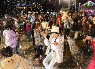 空から舞い散る人工雪に歓声を上げて喜ぶ子どもたち=22日午後7時17分、沖縄市・沖縄こどもの国(田嶋正雄撮影)