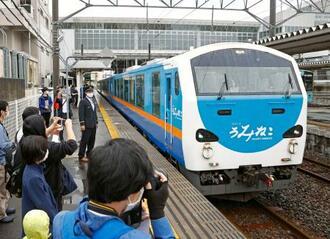ファンらに見送られ、JR八戸駅を出発する観光列車「リゾートうみねこ」=26日、青森県八戸市