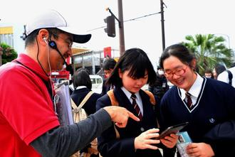 タブレットを手に、街ガイドの案内でまちあるきをする生徒たち=1日、沖縄市